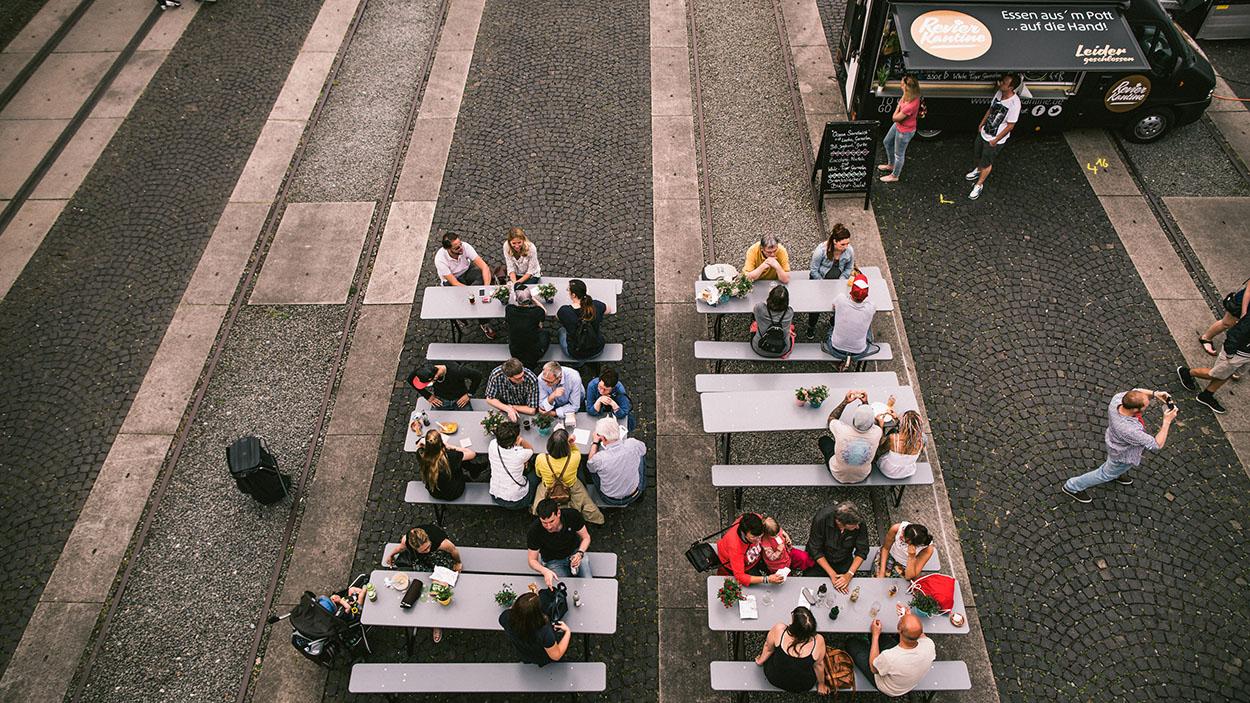 Street Food Markt auf Zeche Zollverein. Besucher sitzen an Biertisch